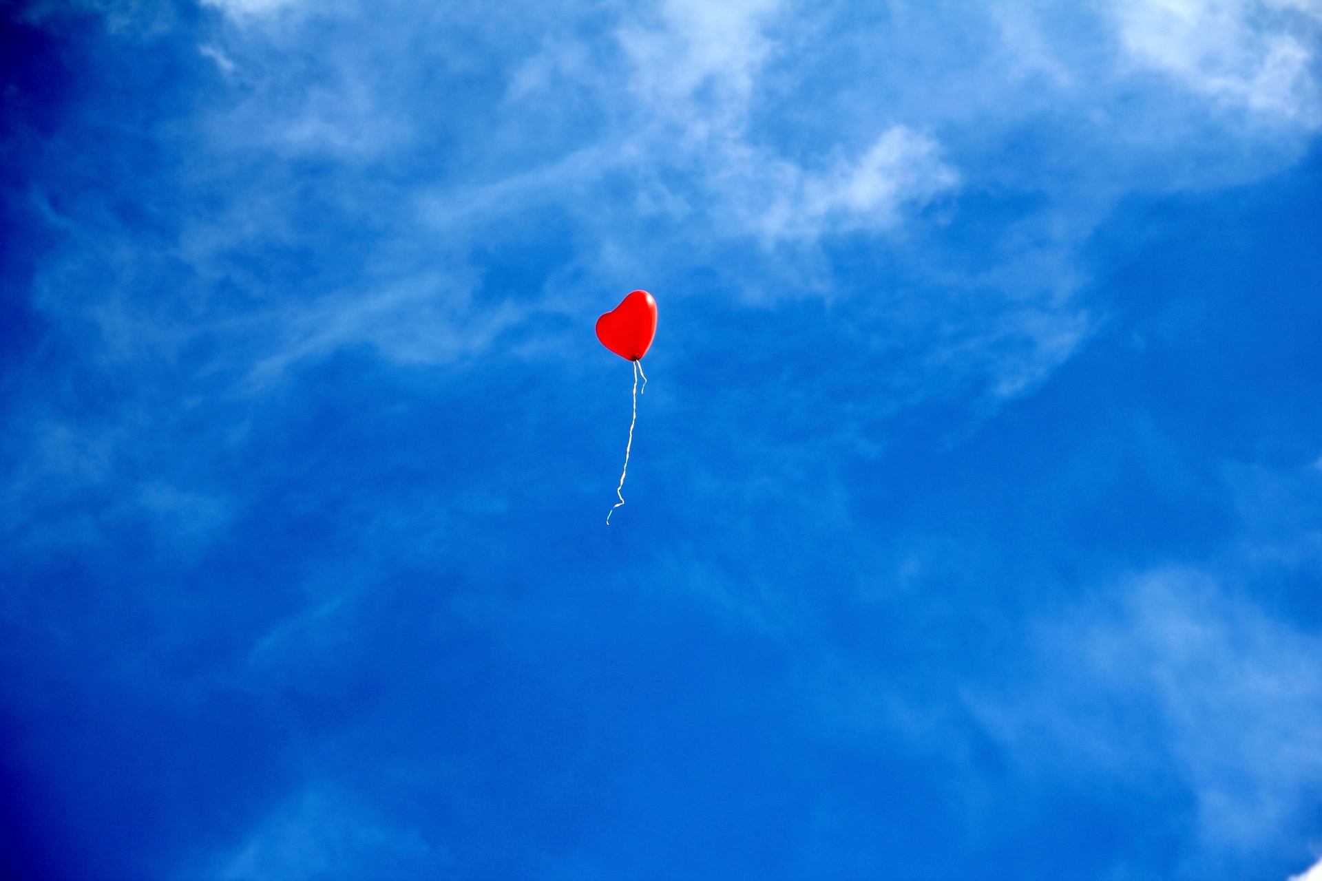 Photo of a red heart shaped balloon in a blue sky